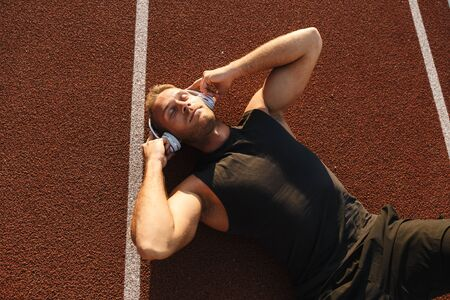 Image of athletic sportsman listening to music with headphones while lying at running track outdoors