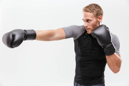 Confident young fit sportsman wearing boxing gloves isolated over white background, boxing Stock Photo - 134448622