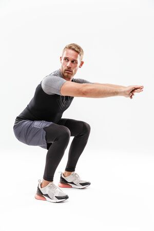 Full length of a handsome young concentrated sportsman doing squats while standing isolated over white background
