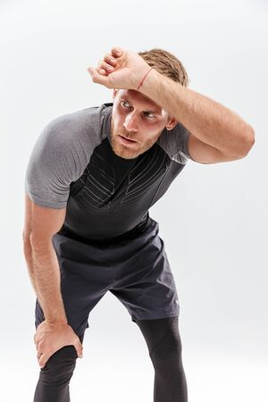 Portrait of a tired fit sportsman resting after work out isolated over white background