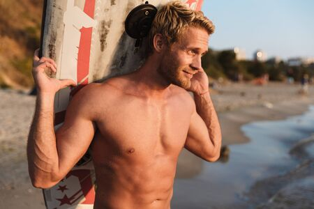 Image of cheerful young shirtless surfer man carrying his surfboard by ocean at sunrise Stock Photo