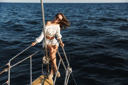 Image of a gorgeous young pretty positive woman posing outdoors on yacht in sea.