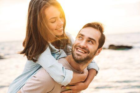 Bild eines jungen glücklichen Mannes, der Huckepack-Fahrt gibt und eine schöne Frau beim Gehen am sonnigen Strand betrachtet