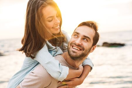Image of young happy man giving piggyback ride and looking at beautiful woman while walking on sunny beach