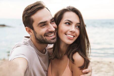 Foto eines lächelnden jungen Paares, das sich umarmt und ein Selfie-Foto macht, während es sich am sonnigen Strand ausruht? Standard-Bild