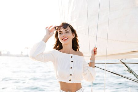 Photo of amazing happy cheery pretty woman outdoors posing on yacht in sea.