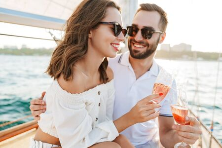 Image of a happy optimistic cheery young loving couple outdoors on yacht in sea.