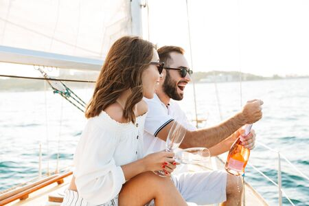 Image of a positive optimistic happy young loving couple outdoors on yacht in sea drinking champagne.