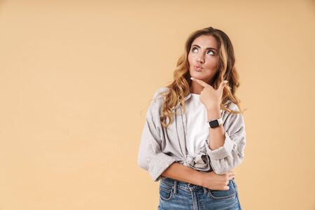 Image of pretty brunette woman wearing casual clothes thinking and looking upward at copyspace isolated over beige background