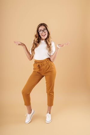 Full length image of joyous woman wearing eyeglasses smiling and gesturing arms aside isolated over beige background in studio