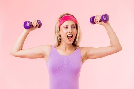 Image of delighted young woman in headband holding dumbbells and winking isolated over pink background