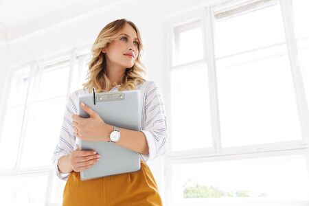 Image of successful elegant secretary woman holding clipboard in white office