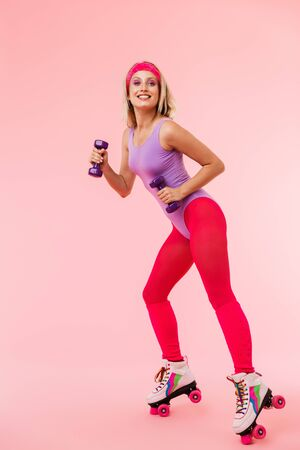 Image of pleased seductive woman in retro roller skates holding dumbbells and smiling isolated over pink background Zdjęcie Seryjne