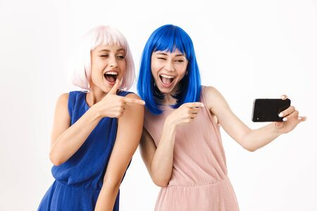 Portrait of two funny women wearing blue and pink wigs taking selfie photo and pointing fingers at cellphone isolated over white background Stockfoto