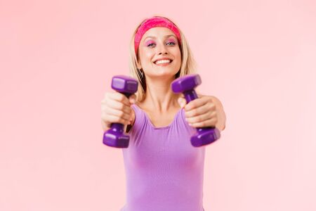 Image of happy young woman in headband holding dumbbells and smiling isolated over pink background