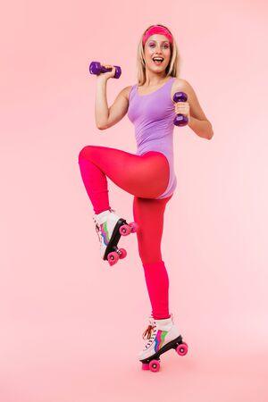 Image of joyful seductive woman in retro roller skates holding dumbbells and smiling isolated over pink background Zdjęcie Seryjne