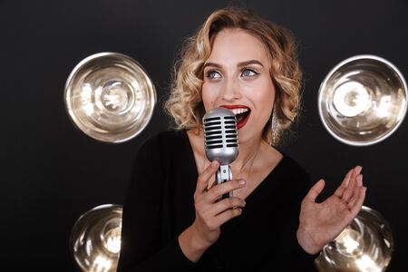 Image of caucasian artist woman in elegant dress singing into microphone over lights background 写真素材