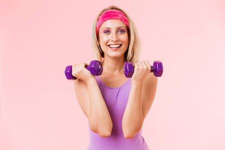 Image of happy attractive woman in headband holding dumbbells and smiling isolated over pink background Zdjęcie Seryjne