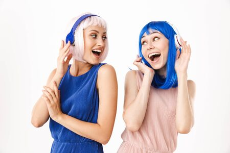 Portrait of two ecstatic women wearing blue and pink wigs listening music with headphones isolated over white background Banco de Imagens