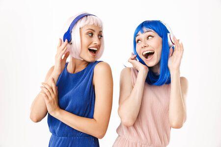 Ritratto di due donne estatiche che indossano parrucche blu e rosa che ascoltano musica con le cuffie isolate su sfondo bianco Archivio Fotografico