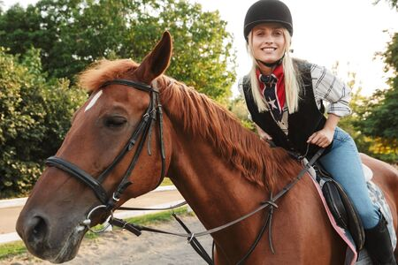 Image of lovely young blonde woman wearing hat riding horse at yard in countryside