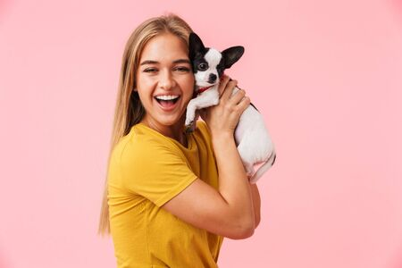 Cute lovely cheerful girl playing with her pet chihuahua isolated over pink background