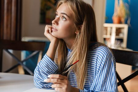 Photo of a thinking dreaming young cute girl at home at the table writing notes in notebook.