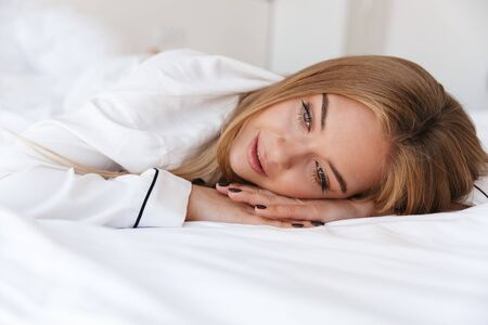Photo of lovely beautiful woman in pajama looking aside while lying on bed after sleep or nap