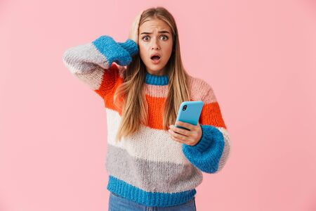 Confused young girl wearing sweater holding mobile phone, shrugging shoulders isolated over pink background