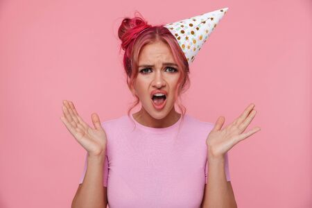 Portrait of irritated young woman wearing party cone screaming and raising arms isolated over pink background