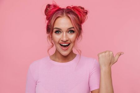 Portrait of excited young woman in t-shirt smiling and pointing finger aside at copyspace isolated over pink background