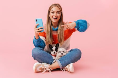 Cute lovely girl wearing sweater sitting with legs crossed with her pet chihuahua and lapdog isolated over pink background, pointing at mobile phone Reklamní fotografie