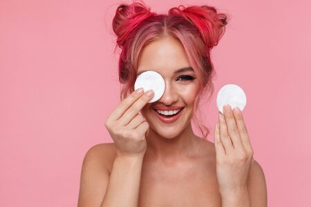 Portrait of positive shirtless young woman cleaning her face with cotton pads isolated over pink background