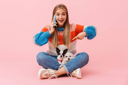 Cute lovely girl wearing sweater sitting with legs crossed with her pet chihuahua and lapdog isolated over pink background, pointing finger at dogs while talking on mobile phone