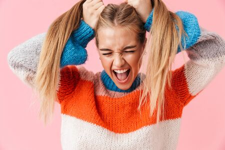 Portrait of an annoyed blonde girl wearing sweater screaming isolated over pink background, pulling her hair out