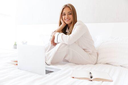 Foto de mujer joven sonriente en pijama mirando a la cámara mientras está sentado en la cama con un portátil y un diario en la habitación de la luz