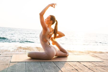 Image of fitness amazing woman outdoors on beach with fitness rug make stretching exercise. Imagens