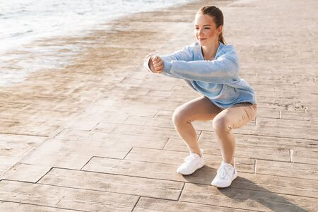 Image of young concentrated pretty fitness woman outdoors on beach make yoga sport squats exercise.
