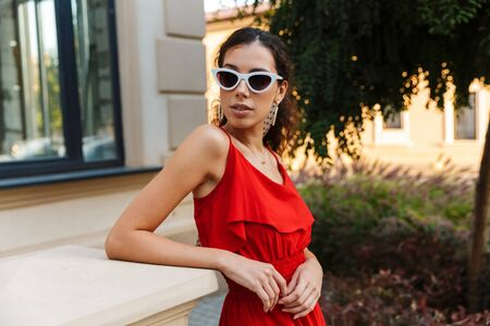 Image of serious attractive woman wearing red dress and sunglasses posing near building outdoors Фото со стока