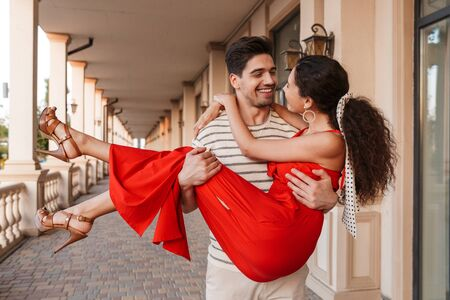 Image of happy romantic man carrying woman in hands and smiling while walking near beautiful building Stockfoto