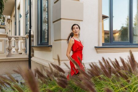 Image of nice beautiful woman wearing red dress looking aside while walking near building outdoors