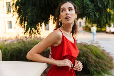 Image of serious attractive woman wearing red dress posing and looking aside near building outdoors Фото со стока