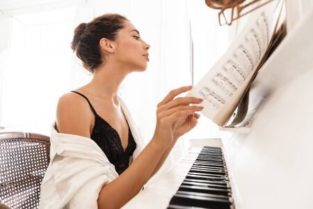 Image of a beautiful young lady in lingerie and white shirt play the piano indoors at home. Foto de archivo