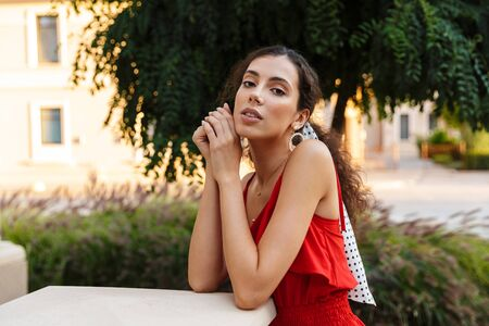 Image of confident charming woman wearing red dress posing and looking at camera near building outdoors Фото со стока