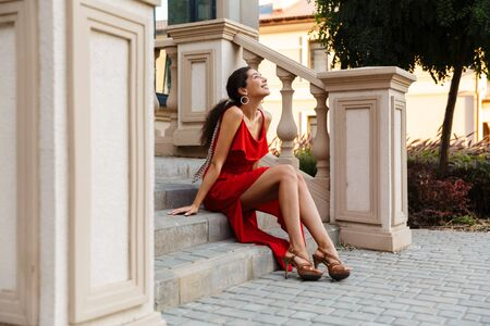 Image of happy caucasian woman wearing red dress smiling and looking upward while sitting on stairs outdoors