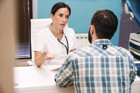 Picture of beautiful serious doctor talking with patient in hospital at the table.