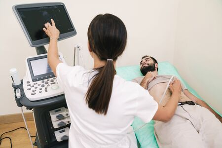 Image of young man getting abdominal ultrasound scan by female doctor in medical uniform at hospital