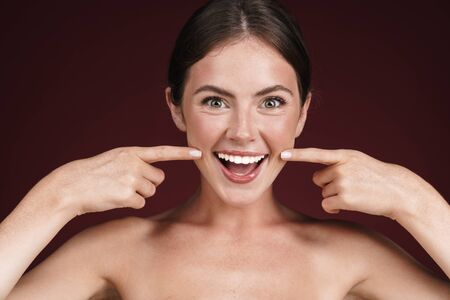 Image of funny half-naked woman laughing and pointing fingers at her cheeks isolated over dark red background Stock fotó
