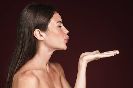 Image in profile of young half-naked woman holding copyspace and making kiss lips isolated over dark red background Stock fotó