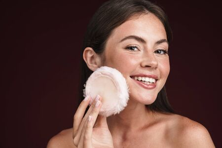 Image of cheerful half-naked woman smiling and using powder sponge isolated over dark red background Stock fotó